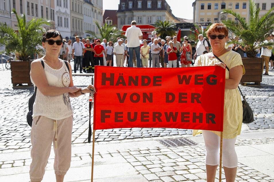 """Die Protestler fordern auf einem Banner """"Hände weg von der Feuerwehr"""". Mehr als 100 Bürger nahmen an der Kundgebung teil."""