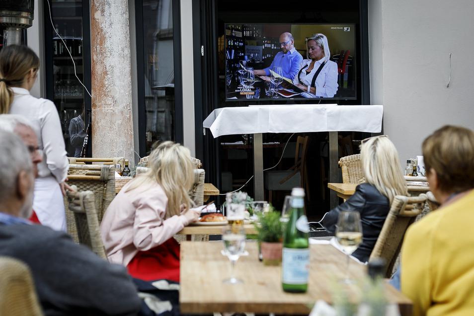 Angestellte und Gäste des Casa Nova schauen die Fernsehsendung Mein Lokal Dein Lokal, in dem es um das Restaurant geht, in dem sie sitzen.