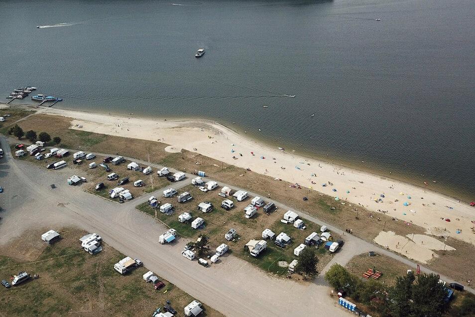 Badegäste genießen die Sonne am Strand eines Campingplatzes an der Bleilochtalsperre.