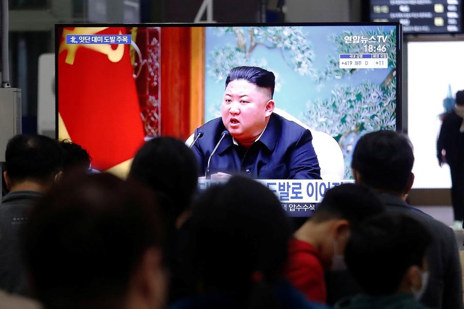 Menschen schauen auf einen Bildschirm im Bahnhof Suseo, auf dem ein Bild des nordkoreanischen Machthabers Kim Jong Un während einer Nachrichtensendung gezeigt wird.