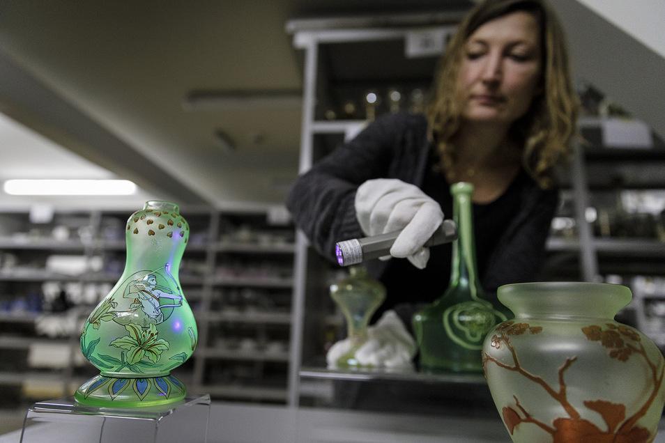 Manches Glas leuchtet unter UV-Licht durch seine bestimmte Zusammensetzung. SZ-Redakteurin Ines Eifler probiert das im Depot des Schlesischen Museums aus.