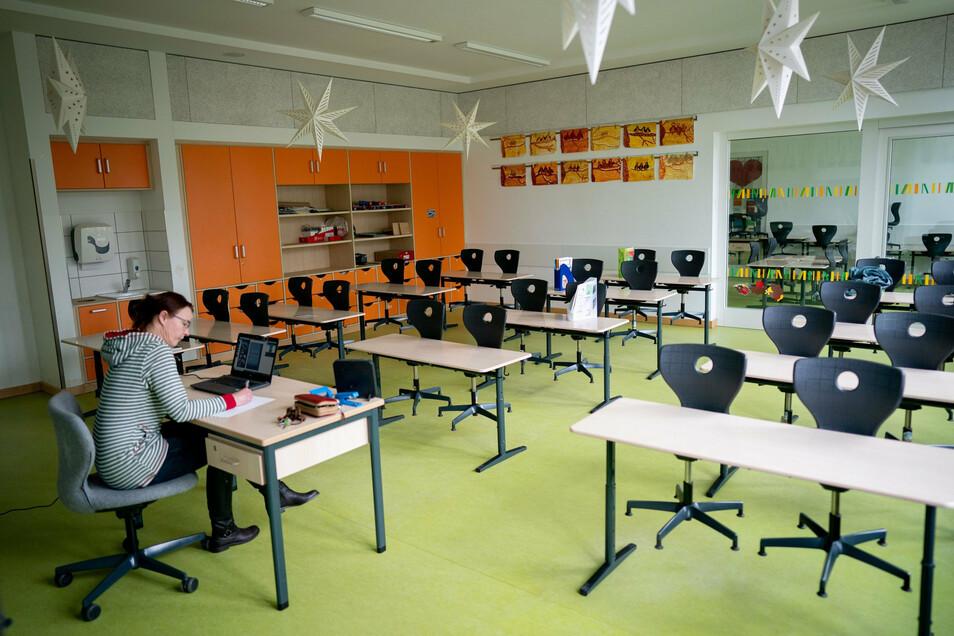Eine Lehrerin sitzt in ihrem leeren Klassenzimmer vor einem Laptop.