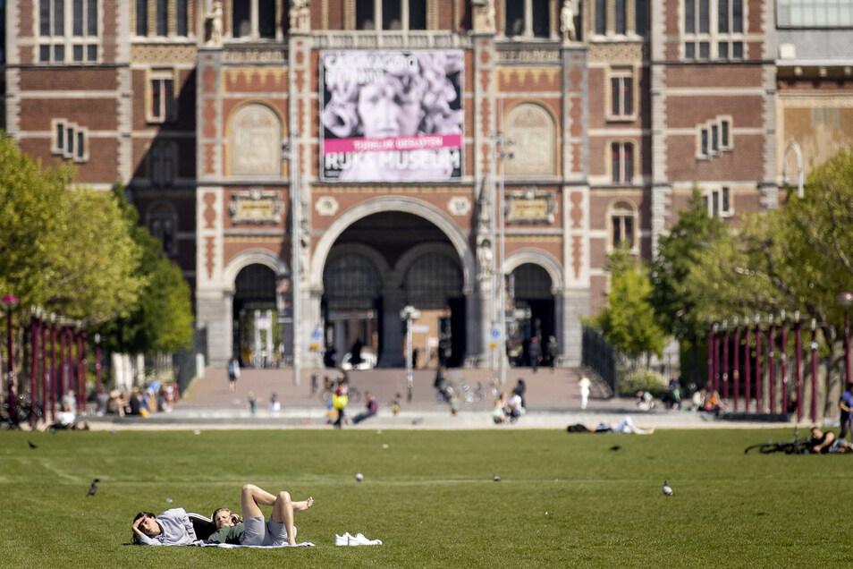 Auf dem Rasen von Museumplein in Amsterdam liegen Menschen.Ein Niederlande-Besuch wird im Sommer wohl möglich sein.