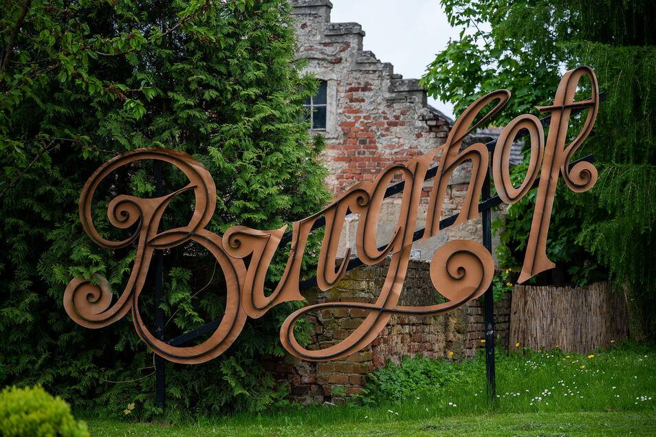 Die historische Reklame des Burghofes steht jetzt im Garten des Anwesens.