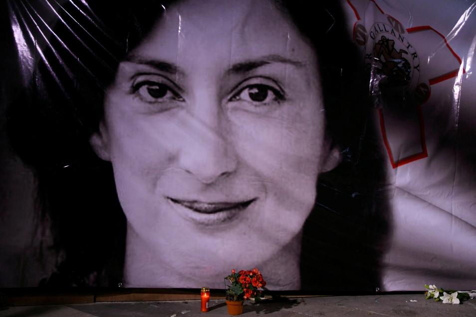 Blumen und eine Kerze liegen vor einem Porträt der getöteten Enthüllungsjournalistin Daphne Caruana Galizia während einer Mahnwache vor dem Justizpalast in Valletta, Malta.