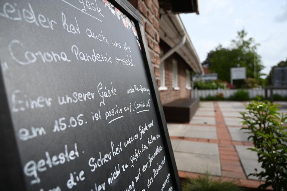 """Niedersachsen, Leer: Ein Schild mit der Aufschrift """"Leider hat auch uns die Corona Pandemie erreicht."""" steht vor dem Restaurant """"Alte Scheune"""". Nach dem Besuch des Lokals sind 23 Gäste positiv auf das Coronavirus getestet worden."""