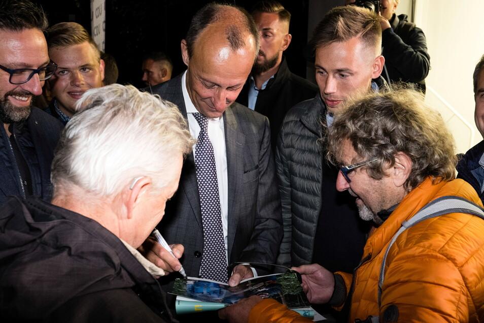 Der verhinderte CDU-Kanzlerkandidat Friedrich Merz (Mitte) gibt in der Görlitzer Landskronbrauerei in Görlitz Autogramme. Neben ihm steht CDU-Direktkandidat Florian Oest, den er im Wahlkampf unterstützt.