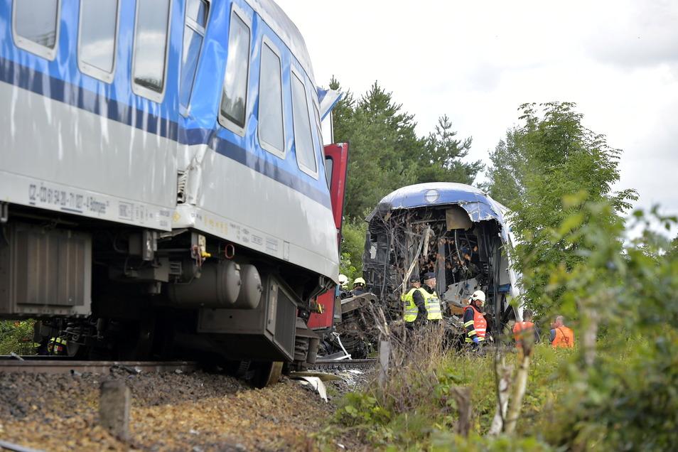 Einsatzkräfte stehen an einem entgleisten Waggon. Ein aus München kommender Expresszug ist in Tschechien mit einem Personenzug zusammengestoßen.