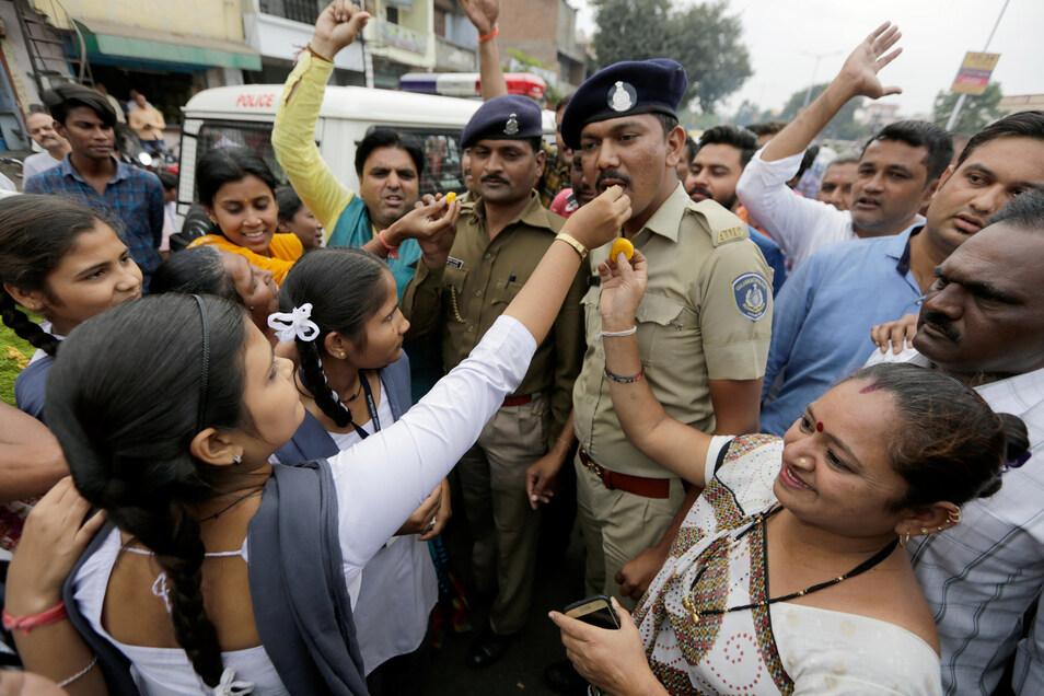 Indische Frauen bieten Polizisten Süßigkeiten an zur Feier der vier toten mutmaßlichen Vergewaltiger.