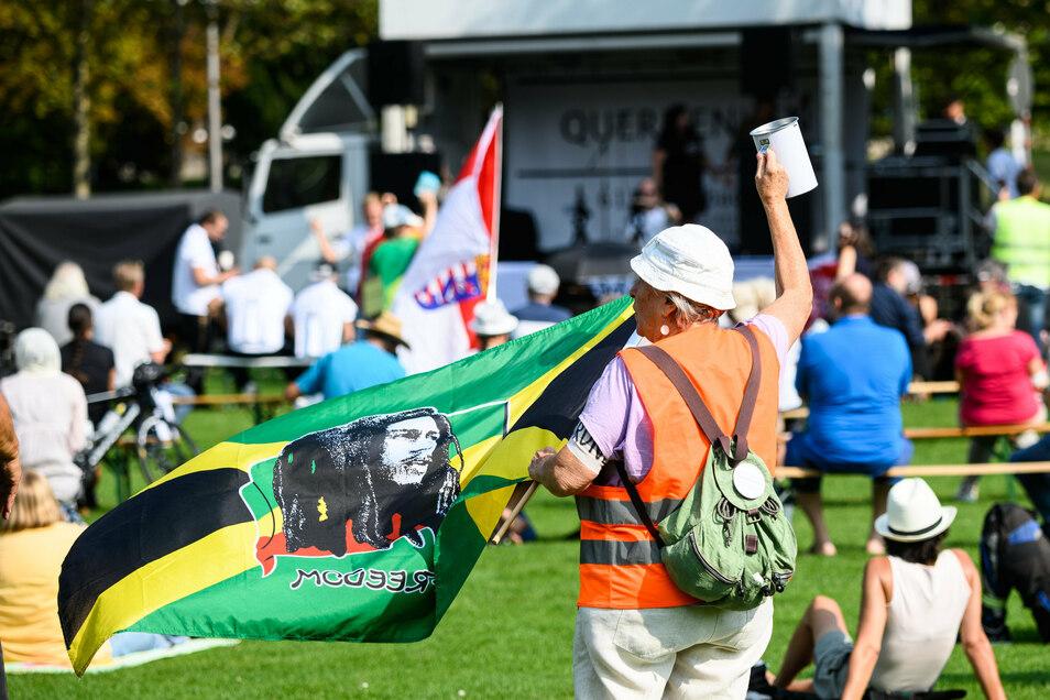 """Eine Frau sammelt bei einer Kundgebung gegen die staatlichen Corona-Regeln mit """"Bob Marley-Flagge"""" Spenden für die Initiative """"Querdenken""""."""