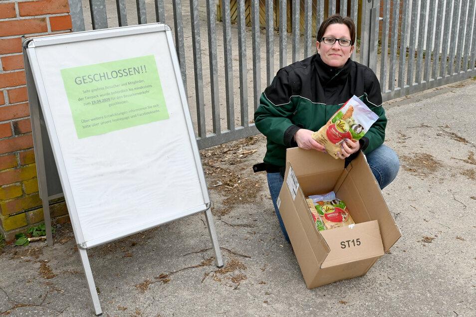 Verena Caspari zeigt einen von einem Spender vor dem geschlossenen Tor abgestellten Karton mit Kaninchenfutter.