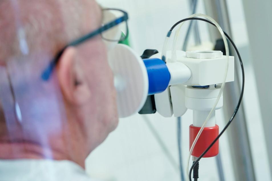 Ein von einer Corona-Erkrankung genesener Patient bekommt in einer Lungentest-Kabine in einer Rehaklinik die Lungenfunktion gemessen. Long Covid soll etwa jeden Zehnten Coronainfizierten betreffen.