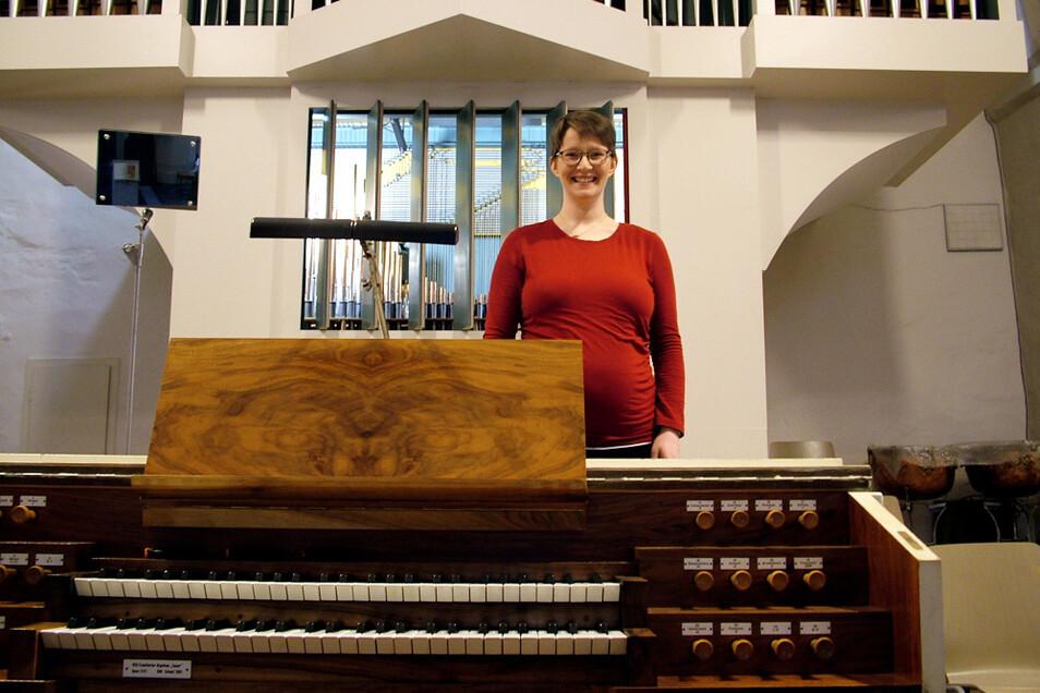Claudia Hofmann, die derzeit ihr erstes Kind erwartet, hinter ihrem Arbeitsplatz und vor ihrem Arbeitsgerät – zwischen dem Spieltisch und der Orgel der katholischen Wittichenauer Pfarrkirche St. Mariä Himmelfahrt.