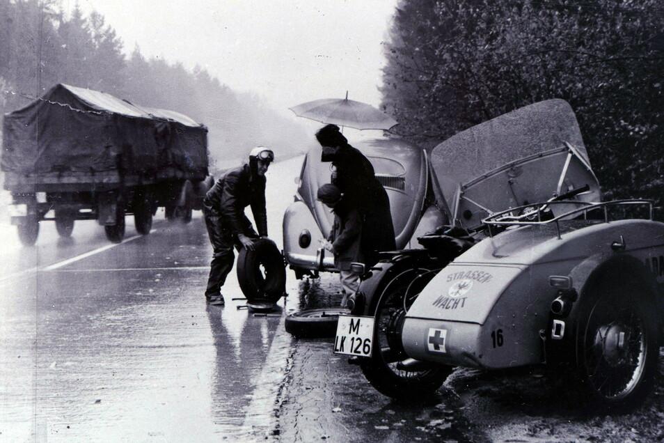Pannenhilfe 1955 in der alten Bundesrepublik: Hier wechselt ein ADAC-Mann unweit von München im strömenden Regen das Rad an einem VW Käfer.
