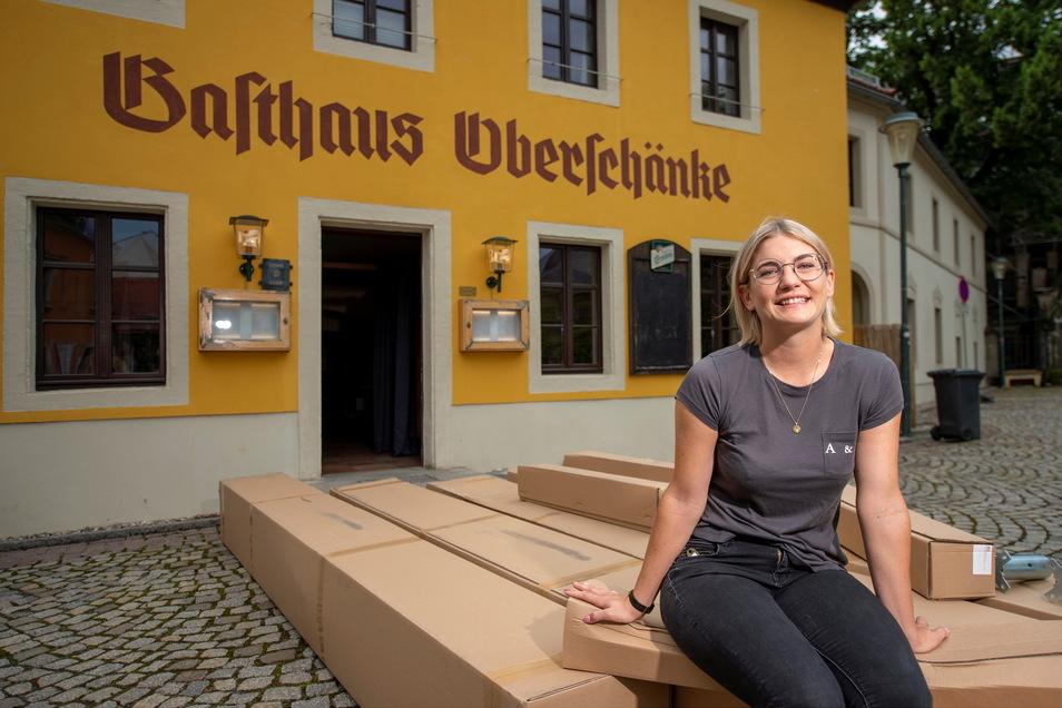 Sitzt auf den gerade gelieferten neuen Sonnenschirmen für die Terrasse - Alisa Zuber, die neue Wirtin der Oberschänke in Altkötzschenbroda.
