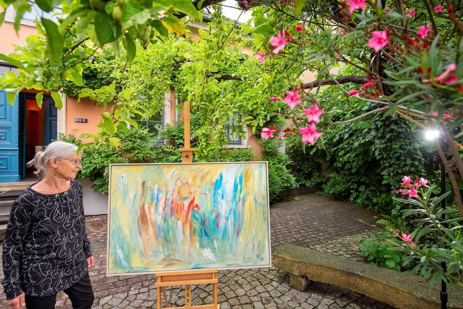 """Gerlinde Queißer betrachtet in ihrem Garten das Bild """"Summertime"""" ihres Mannes Max Manfred Queißer. Am 17. und 18. Juli dieses Jahres zeigt sie in den Nachmittagsstunden weitere Arbeiten."""