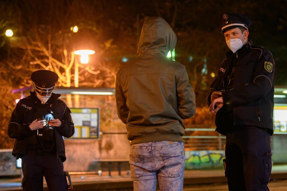 Polizisten überprüfen in der Nacht im Dresdner Stadtteil Gorbitz im Rahmen einer Kontrolle der Corona-Ausgangssperre einen Mann.