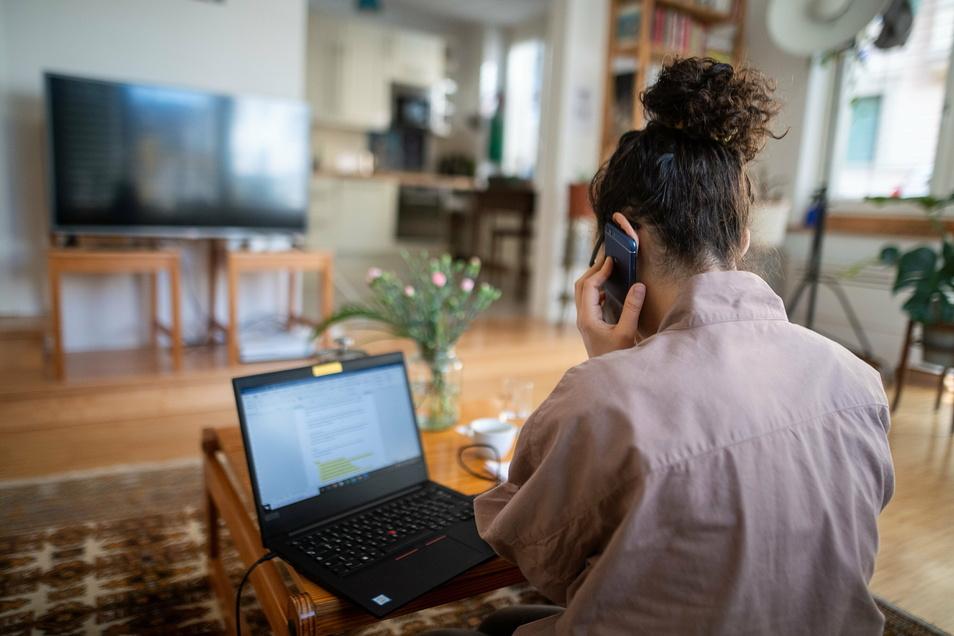 Eine junge Frau im Homeoffice nimmt in ihrem Wohnzimmer an einer Telefonkonferenz teil, hier ein Symbolbild.
