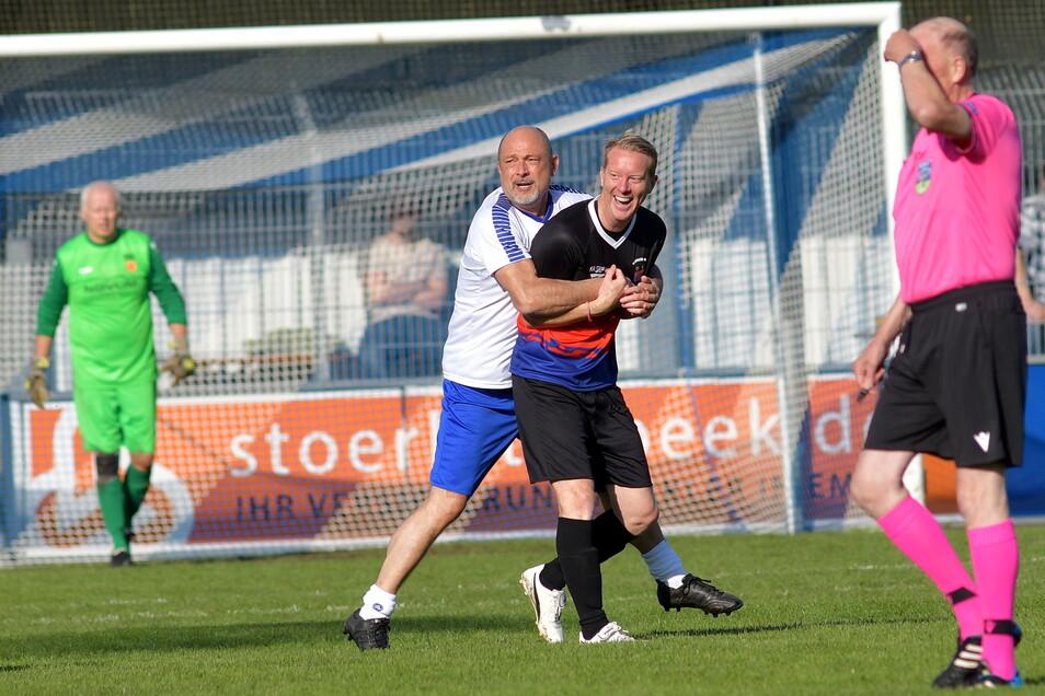 Ein bisschen Spaß muss sein: Der einstige Regionalliga-Spieler Uwe Lüdtke (l) von der DDR-Mannschaft umklammert Timo Schultz, den Trainer des Zweitligisten FC St. Pauli, der für Ostfriesland spielte.