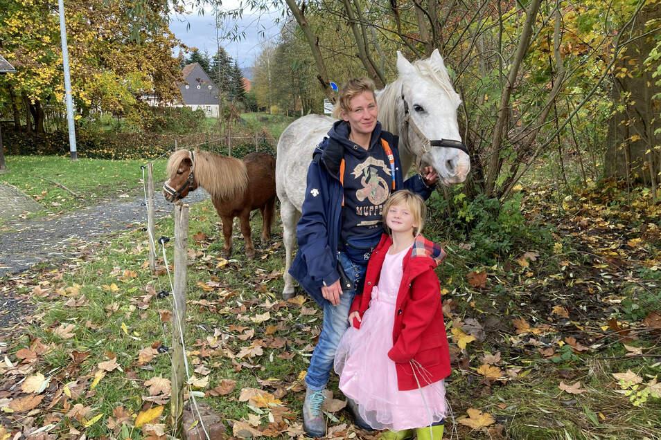 """Stefanie Stiller mit Tochter Hera und ihrem Araber-Schimmel """"Zadkiel"""" und Shetland-Pony """"Bobby"""" auf ihrer Koppel in Großschweidnitz."""