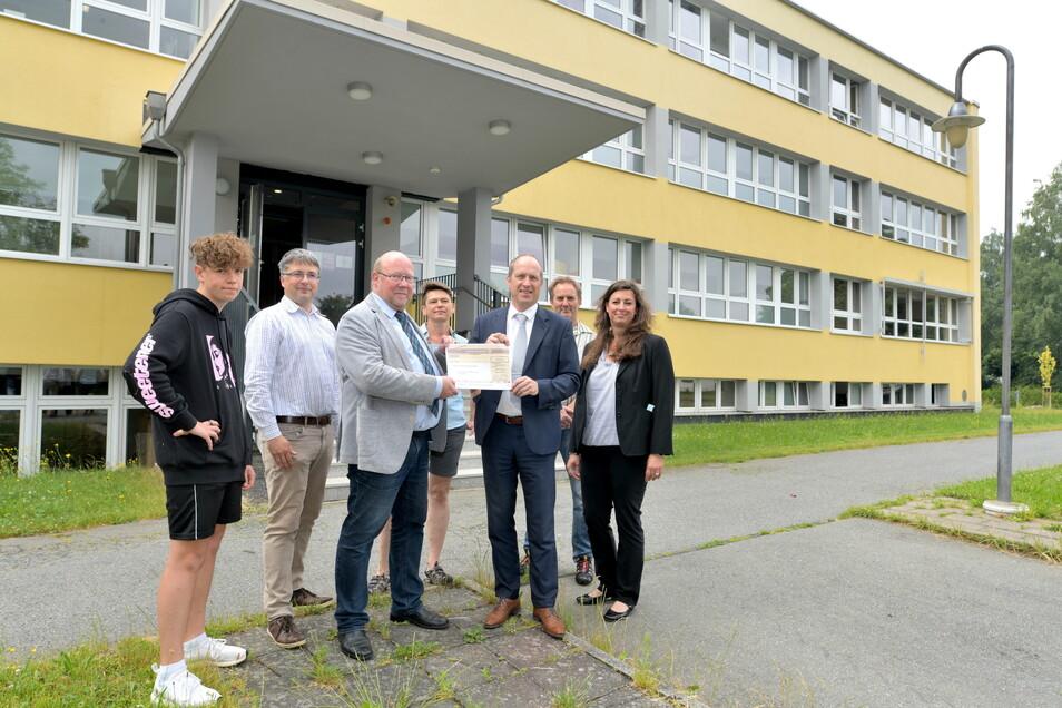 Matthias Lehmann von der Stiftung hat an Schulleiter (3. v. l.) Oberschule Volker Rienäcker einen Scheck über 4.000 Euro übergeben.