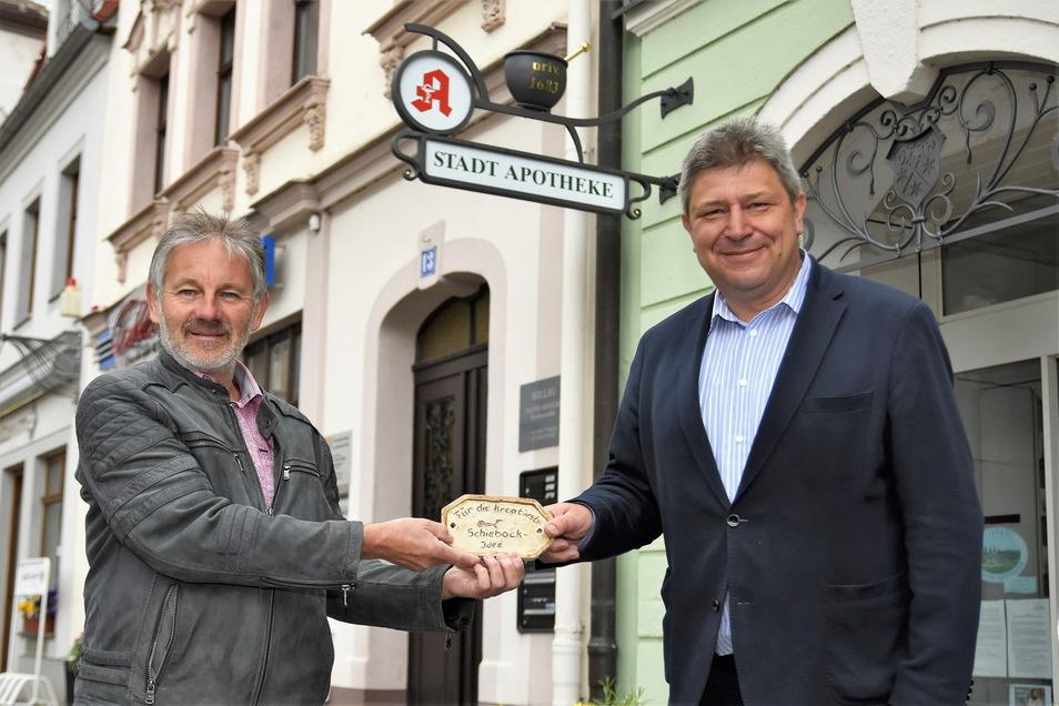 Der Schiebock des Jahres 2020 hängt an der Stadtapotheke. Inhaber Rainer Klotsche (l.) freut sich über die Auszeichnung von Oberbürgermeister Holm Große (Freie Wähler).