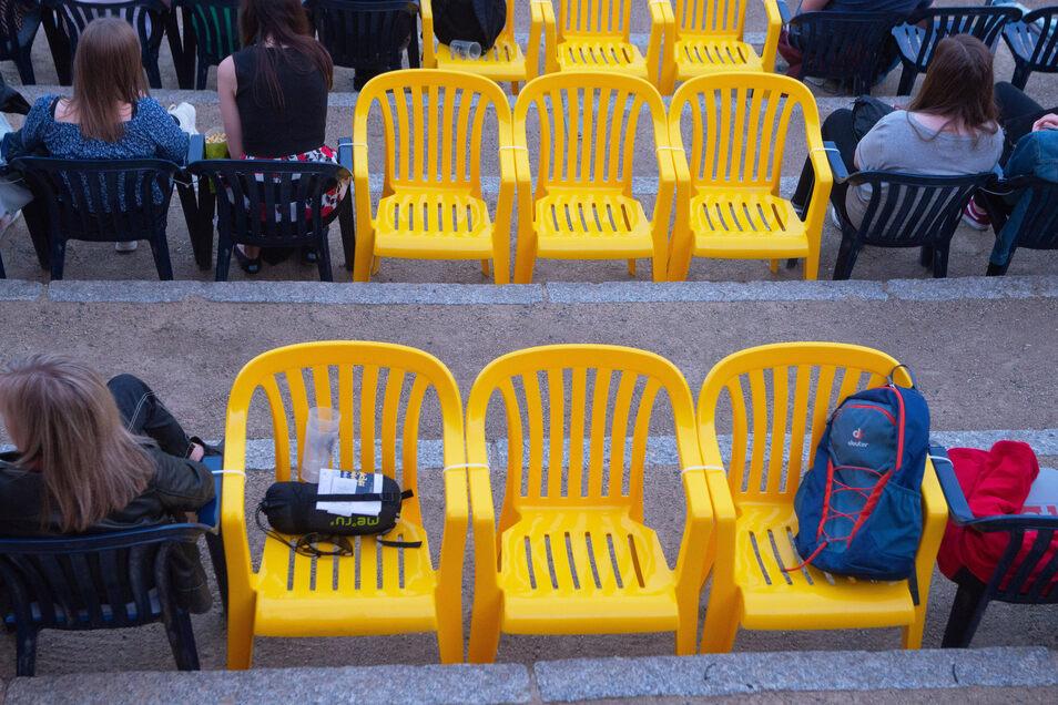 Die gelben Plastikstühle stehen mit dem Rücken zur Leinwand. Sie sorgen dafür, dass man als Kinogast auch genug Abstand zu seinem Sitznachbarn hat.