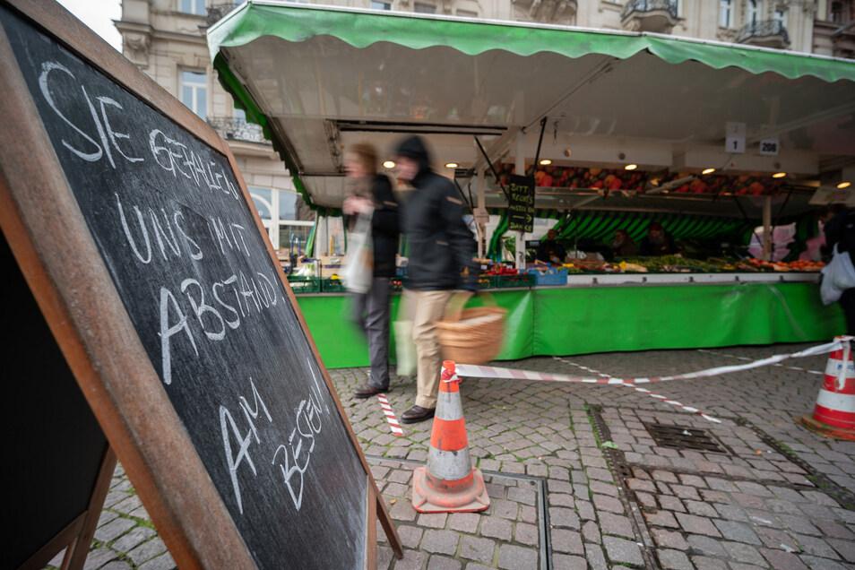 Ein Schild weist auf diesem Wochenmarkt auf die derzeit wichtigste Regel hin: Abstand zu halten