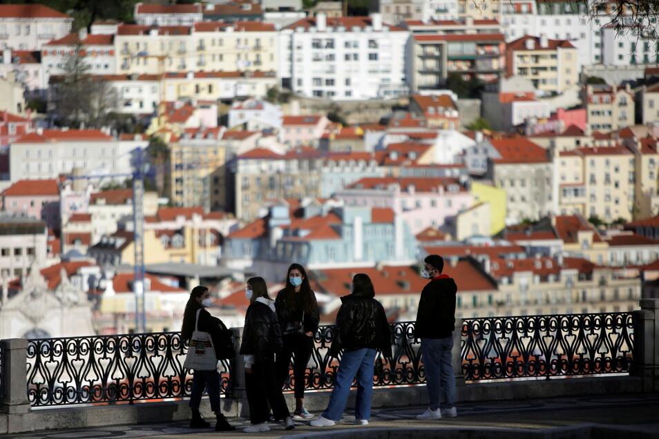 Eine Gruppe junger Menschen mit Mund-Nasen-Schtuz steht an einem Aussichtspunkt mit Blick auf die Altstadt von Lissabon. Weit weg von dort könne sie jetzt nicht: Reisen in und aus dem Großraum Lissabon sind für das Wochenende verboten werden.