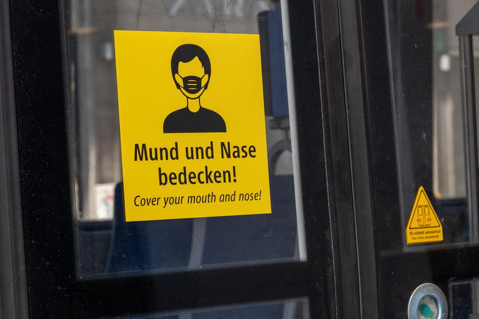 Ein Aufkleber mit der Aufforderung, Mund und Nase zu bedecken, ist in deutscher und englischer Sprache an einer Trambahn in Berlin angebracht.
