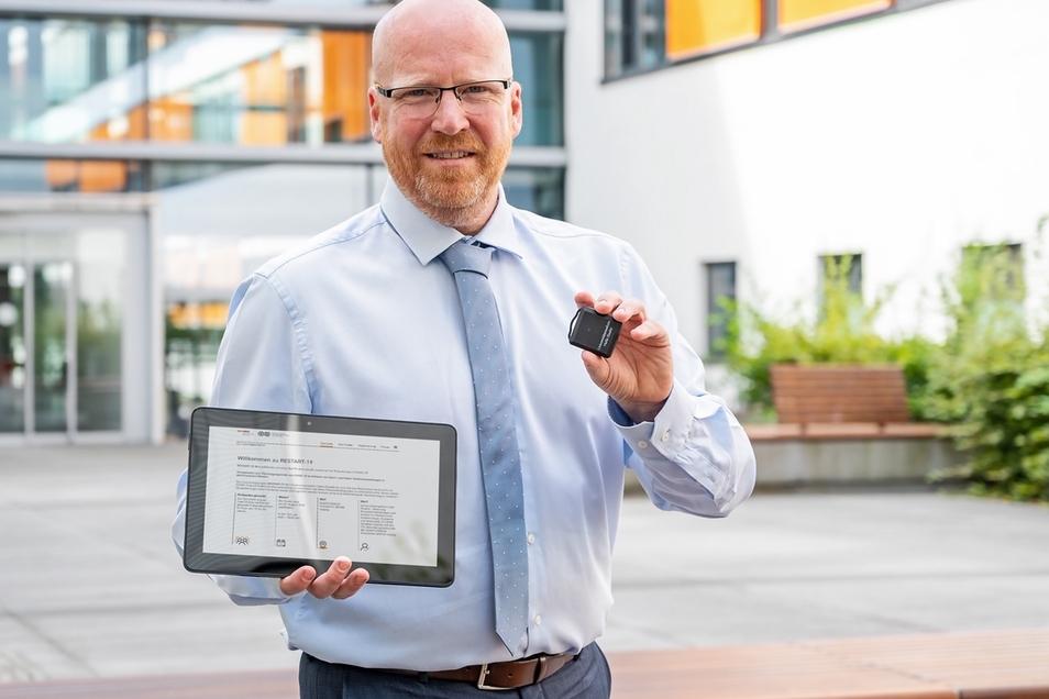 Dr. Stefan Moritz von der Universitätsmedizin Halle zeigt die Projektwebseite für Restart-19 und das Contact Tracing Device, einen Ultrabreitband-Tracker.