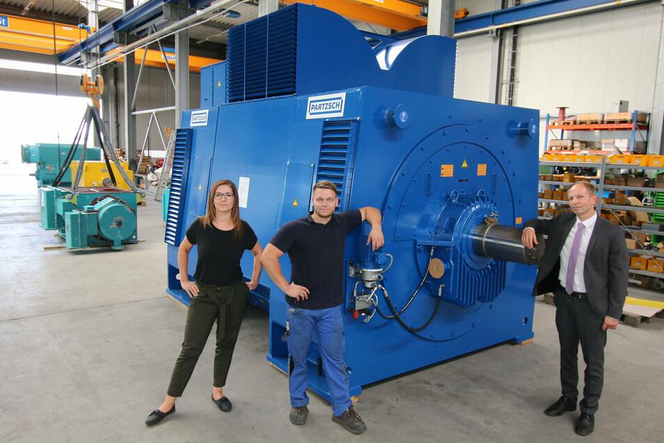 Madlen Gabsch (von links), Assistentin der Geschäftsleitung, Mitarbeiter Tom Büttner und Betriebsleiter Thomas Götze stehen an dem Generator, den Partzsch Elektromotoren für eine Papierfabrik gebaut hat. Er ist der erste große Generator, der komplett