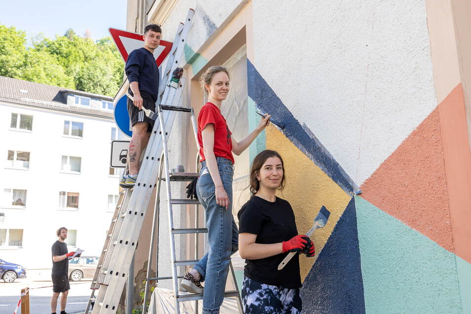 Pauline Domke, Alena Rathke und Martin Lessing (von vorn nach hinten) gestalten die Fassade des leer stehenden Wohn- und Geschäftshauses am Moritz-Großmann-Platz.