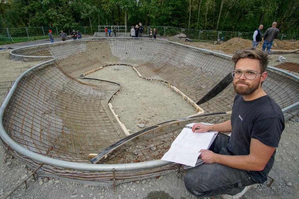 """Der neue Skatepark im Bautzener Stadtteil Gesundbrunnen nimmt Gestalt an: Landschaftsarchitekt Lukas Merkel, hier am sogenannten """"Pool"""", freut sich über den Baufortschritt."""