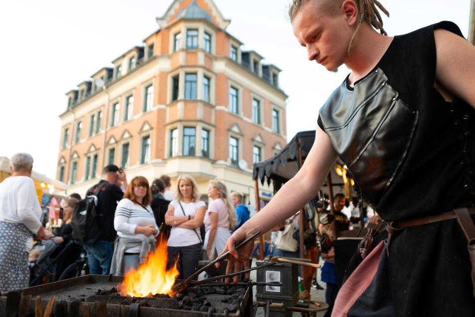 Der Schmied zeigte auf der Hauptstraße seine Handwerkskunst. Zahlreiche Besucher beobachteten ihn bei seiner Arbeit.
