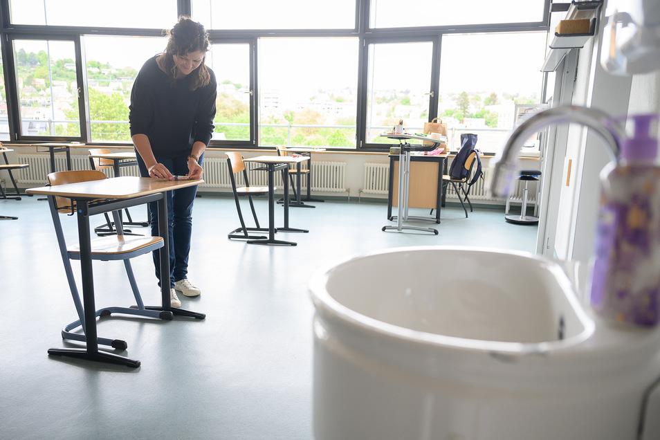 Eine Lehrerin bereitet ein Klassenzimmer für den Unterricht unter Corona-Bedingungen vor.