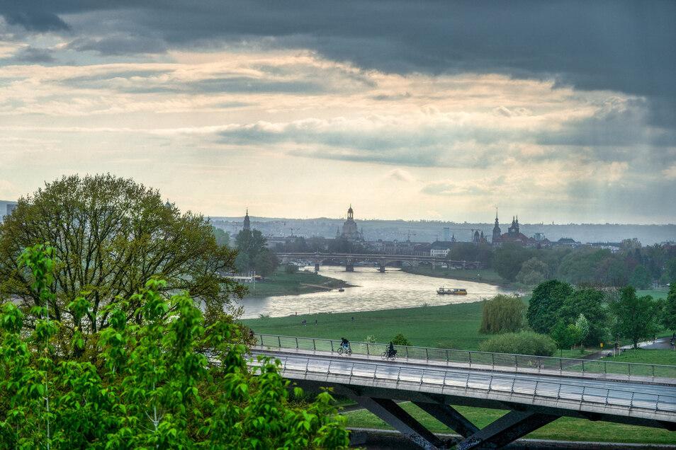 Zwei Radler fahren am Mittwochabend bei strömenden Regen über die Waldschlösschenbrücke in Dresden.