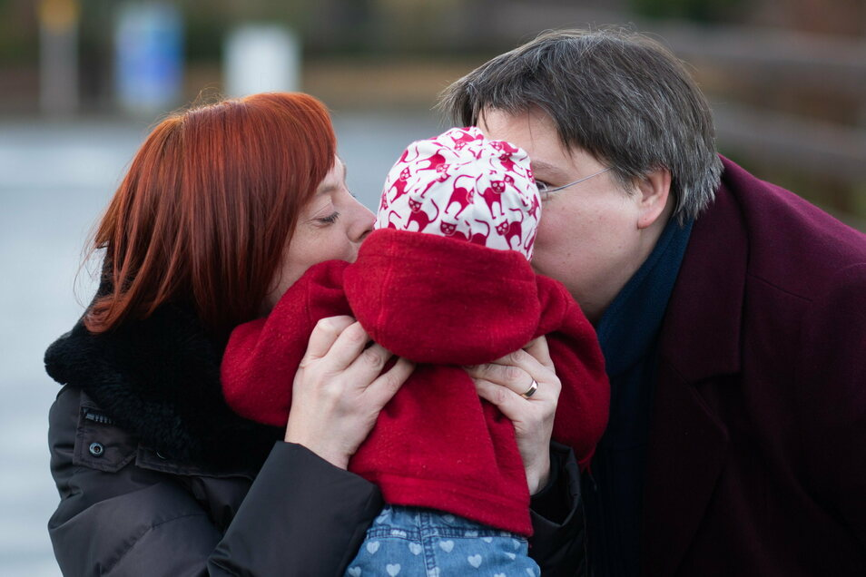 Gesa Teichert-Akkermann (l) und Verena Akkermann geben ihrer Tochter Paula (11 Monate alt) ein Küsschen auf die Wange. Familie Akkermann will über Familiengerichte eine Gleichstellung mit heterosexuellen Paaren bei der Elternschaft erreichen.