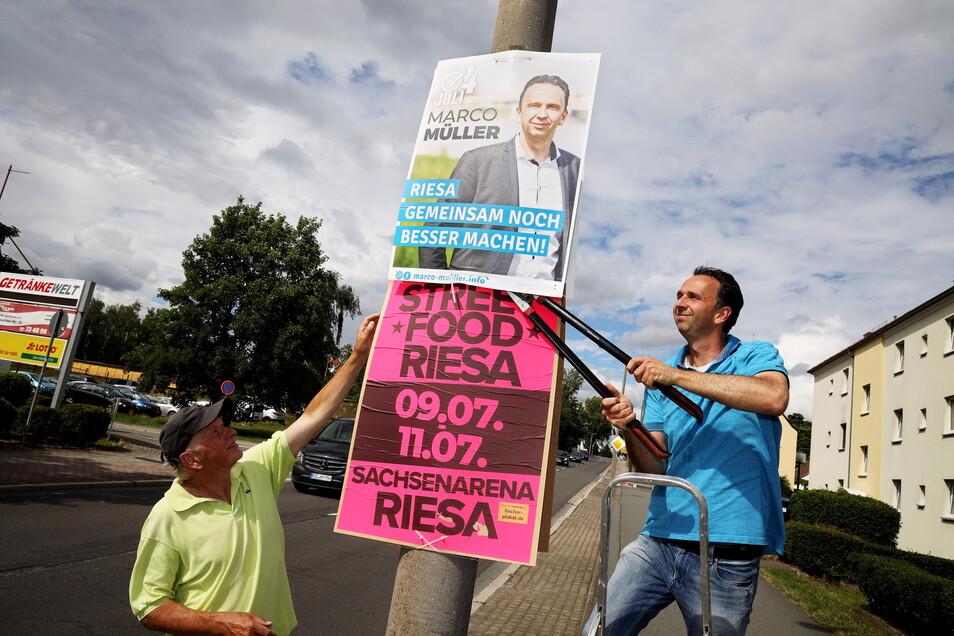 Schnipp, schnapp – da ist es ab: OB Marco Müller (CDU, r.) begann am Montag, seine Plakate von Riesas Straßenlaternen zu holen. Ex-OB-Kandidat Gunnar Hoffmann rief einen Tag nach der Wahl zu einem Malwettbewerb an seinen Plakaten auf.