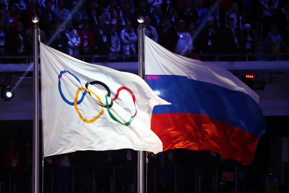 Die olympische Flagge (l) und die russische Flagge (r) wehen während der Abschlussfeier der Olympischen Spiele Sotschi 2014 im Fisht Olympiastadion.