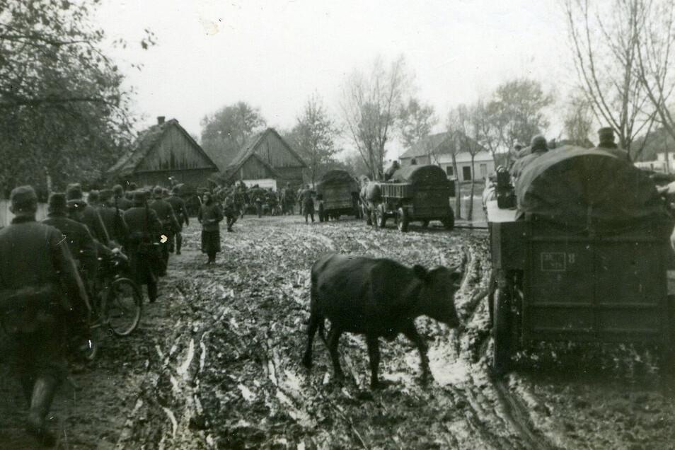 """""""Die Füße werden bleischwer."""" Eine Kolonne von Marcel Weises Bataillon marschiert im Schlamm durch ein russisches Dorf."""