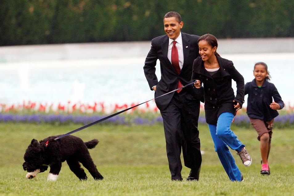 Malia und Sasha Obama spielen 2009 vor dem Weißen Haus mit Hund Bo.