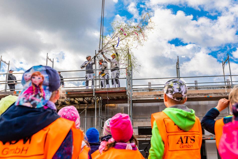 Einige der Kita-Kinder waren zum Richtfest gekommen und hatten eine kleine Birke als Richtkrone mitgebracht. Das Bauwerk bekommt ein begrüntes Flachdach.