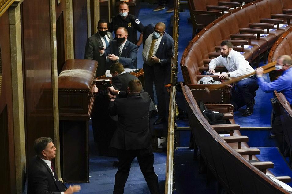 Polizisten stehen mit gezogenen Waffen in der Nähe einer verbarrikadierten Tür, als Demonstranten versuchen, in die Kammer des Repräsentantenhauses im Kapitol einzubrechen.