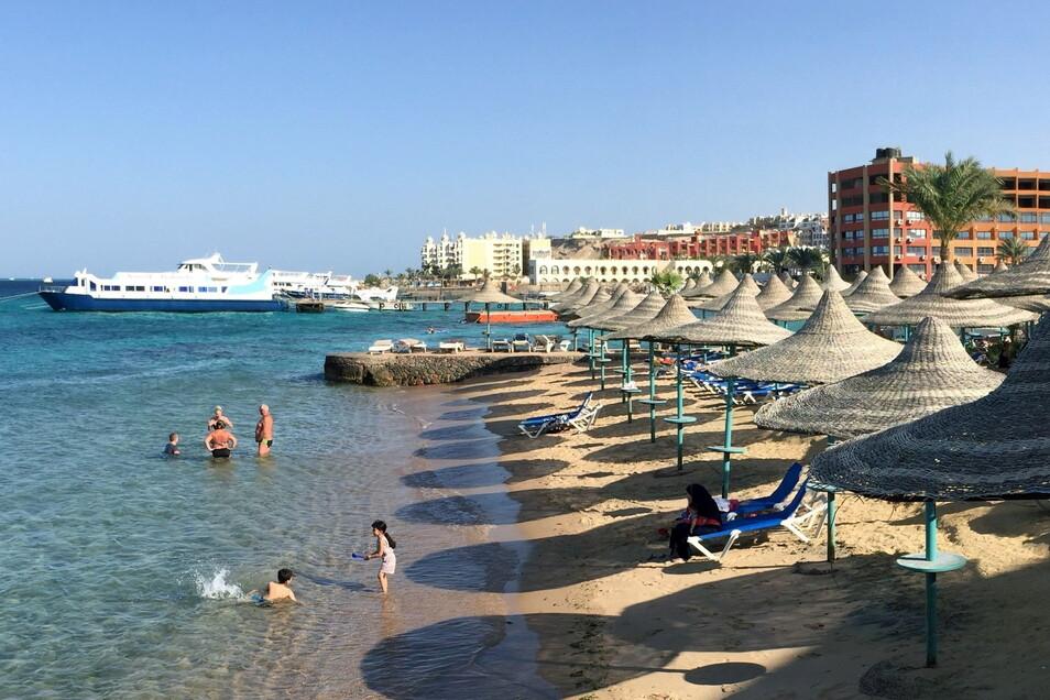 Touristen stehen in Hurghada an einem Hotel-Strand.