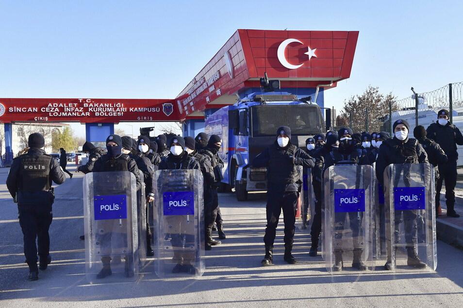 Polizeibeamte mit Schutzausrüstung bewachen den Eingang eines Luftwaffenstützpunktes, nahe eines Gerichtsgebäudes.