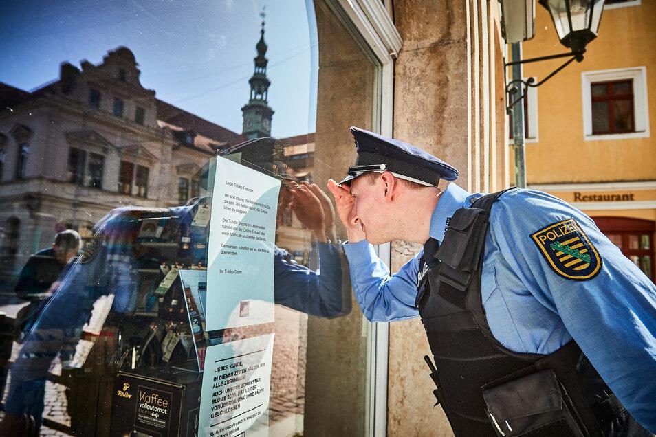 Ist auch wirklich keiner da? Polizist Tobias lugt im geschlossenen Tchiboladen am Pirnaer Marktplatz durch die Scheiben.