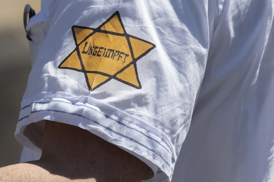 """""""Ungeimpft"""" steht auf einem nachgebildeten Judenstern am Arm eines Mannes, der versucht hatte, sich unter die Teilnehmer einer Demonstration zu mischen, die sich auch gegen Verschwörungstheorien zum Corona-Virus wendet."""