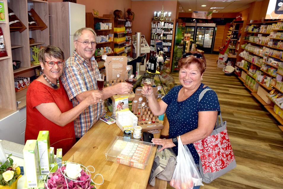 Andrea und Michael Paul vom Reformhaus in Zittau stoßen mit einer Kundin auf die gelungene Renovierung an.