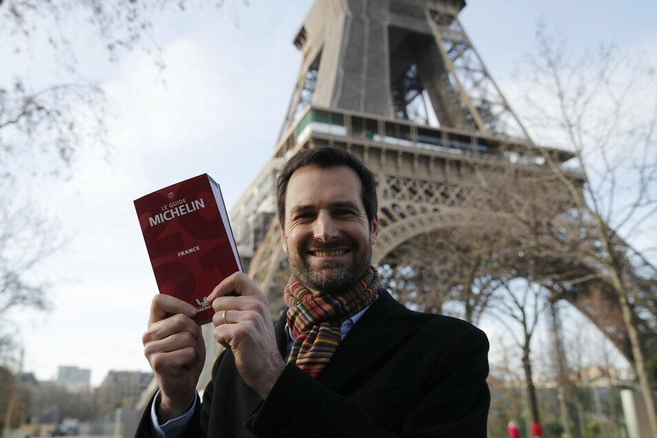 """Gwendal Poullennec, Chef von """"Le Guide Michelin"""", hält vor dem Pariser Eiffelturm die Ausgabe 2021 des Guide Michelin Frankreich in den Händen."""